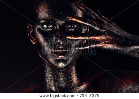 Woman In Black Paint Looking Through Fingers