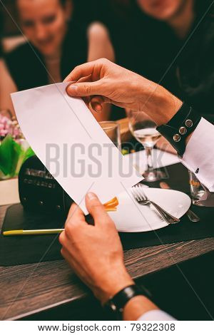 Man Hands Holding Sheet Of Paper In Cafe