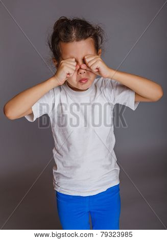 girl baby cries rubs his eyes on a gray background