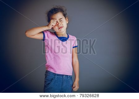 girl child rubs his eyes on a gray background