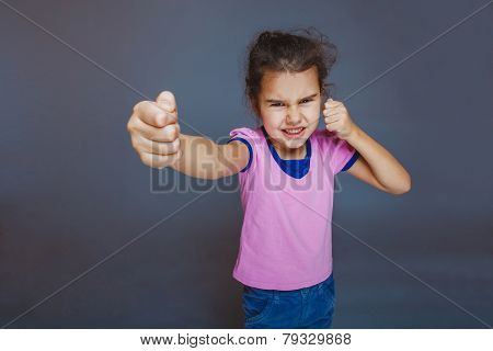 girl getting angry fist shows on a gray background