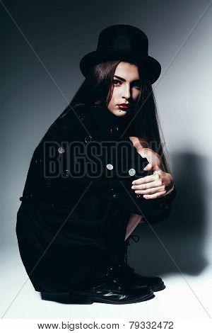 Woman Sitting In Studio In Black Dress