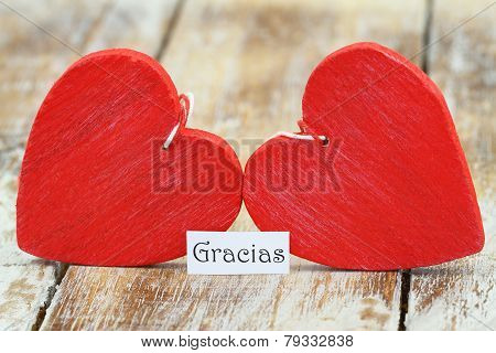 Gracias (which means thank you in Spanish) with two red wooden hearts