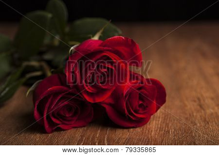 Bouquet Of Roses Lying On A Wooden Table On A Black Background
