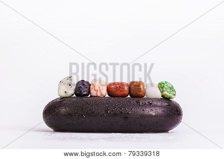 Row Of Chakra Crystals on hot massage black stones
