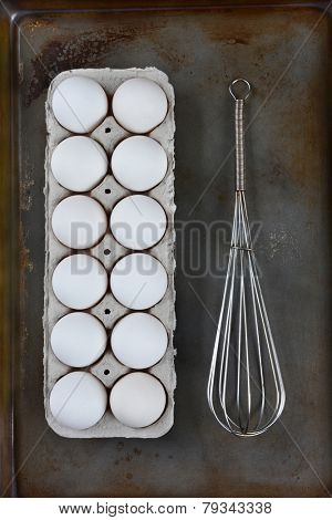 HIgh angle image of a carton of eggs and a wire whisk on a metal baking sheet. Vertical format.