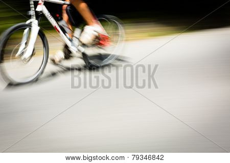 Cyclist on a road bike going fast (motion blur technique is used to convey movement; colour toned image)