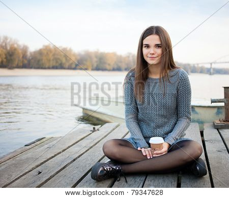 Young beautful brunette woman sitting on the river pier with coffee
