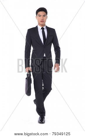 Full body Portrait of a successful young business man carrying a suitcase walking