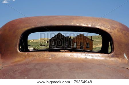 View of Bodie ghost town through rusting car.