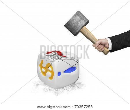 Hand Holding Sledgehammer Hitting White Dice With Dollar Sign