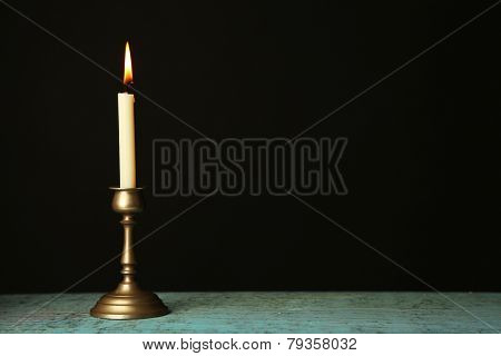 Retro candlestick with candle on wooden table, on black background