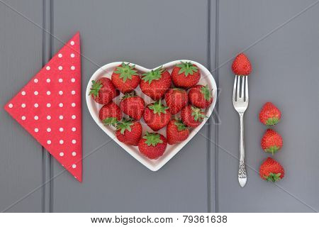Strawberry fruit in a heart shaped dish with polka dot napkin and old silver fork.