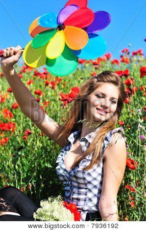 Girl With Windmill In Poppy Field