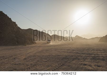 Off Road Vehicle Traveling Through Arid Desert Landscape