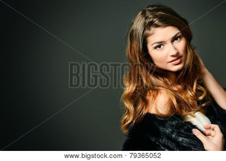Close-up portrait of a magnificent young woman wearing fur jacket. Studio shot. Beauty, fashion. Make-up, cosmetics. Copy space.