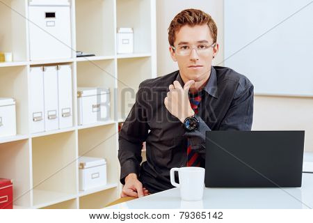 Handsome businessman working at the office on his laptop and pondering something.