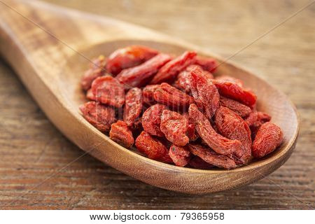dried goji berries on a wooden spoon against a grunge wood, selective focus