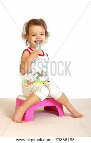 A little girl cleans teeth.