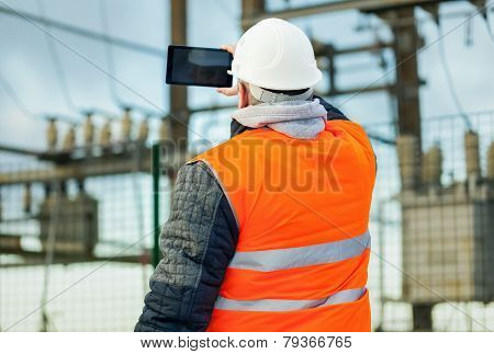 Electrical Engineer with tablet PC in the electric substation