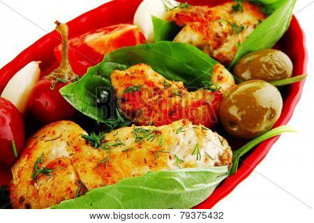 served chicken bbq on red plate with tomatoes and olives