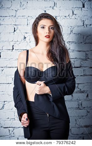Fashion Shot: Beautiful Young Woman In Pants And Jacket Stands At The Wall