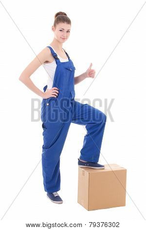 Moving Day Concept - Young Attractive Woman In Blue Coveralls With Cardboard Box Isolated On White