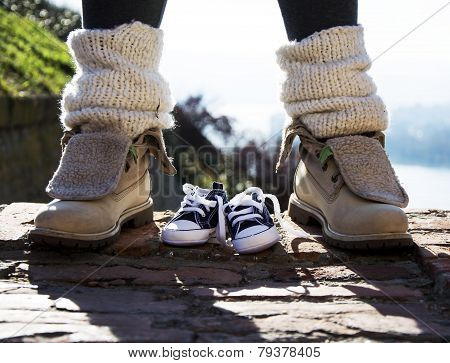 Baby Shoes And Mother Shoes Outdoors On A Stairs