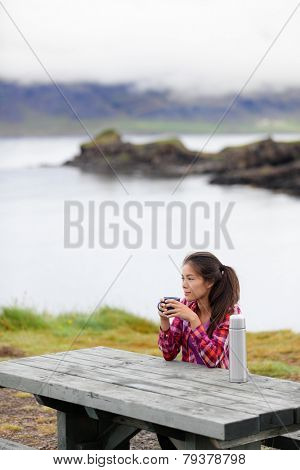 Camping woman sitting at table drinking coffee from thermos bottle flask by lake on Iceland. Camper girl relaxing thinking pensive taking break on road trip in beautiful Icelandic nature.
