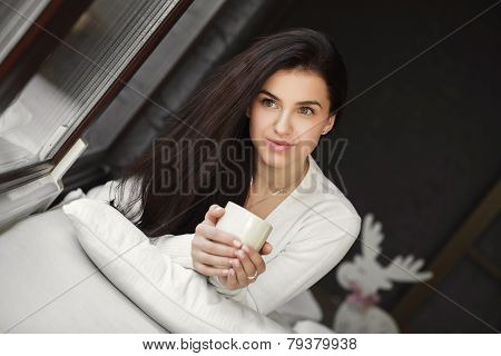 Portrait of a young woman lying in bed at the window with a Cup of coffee.