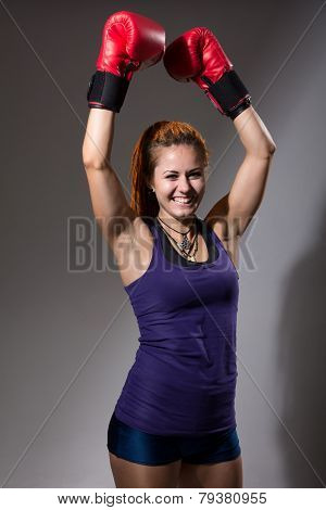 Portrait Of Happy Girl In Boxing Gloves With Raised Hands.