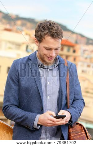Smart phone young urban businessman on smartphone professional using smartphone using app texting sms message on smart phone wearing trendy suit jacket. Caucasian male fashion model.