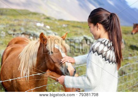 Icelandic horses - woman petting horse on Iceland. Girl in sweater going horseback riding smiling happy with horse in beautiful nature on Iceland.