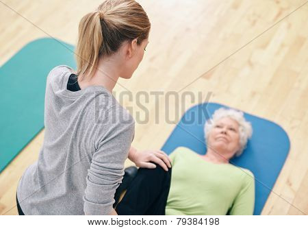 Female Coach Helping Senior Woman Exercising In Gym