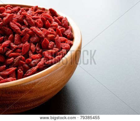 Wooden Bowl Full of Dried Goji Berries on the Dark Table. Healthy Diet