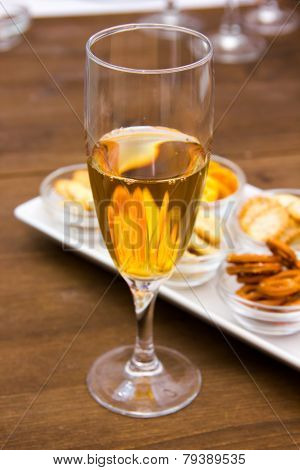 Flute with aperitif and pretzels closely