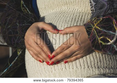 Pregnant Woman Making Heart Shape On A Belly