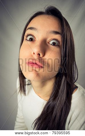 Wide angle distorted funny face of a teenager girl in a kissing expression