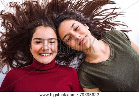 Two joyful teenager girl friends laying on the floor with their heads together