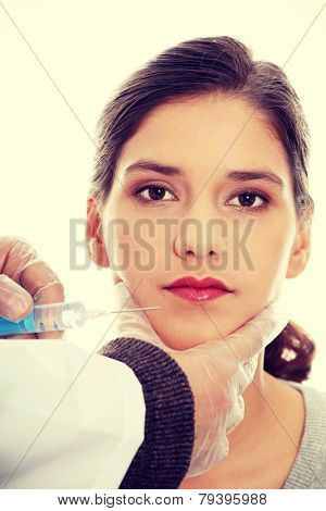 Plastic surgeons giving injection in female skin.