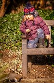 picture of ground nut  - Little girl sitting on a bench in a park and feeding squirrel nuts - JPG