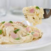 foto of carbonara  - Eating Spaghetti Carbonara noodles pasta meat meal on a plate with fork - JPG