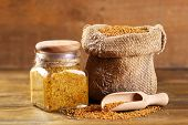 stock photo of mustard seeds  - Mustard seeds in bag and Dijon mustard in glass jar on wooden background - JPG