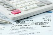 stock photo of statements  - calculator and silver ballpoint pen sitting on a bank statement with focus on the payment due date - JPG