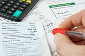 foto of statements  - a persons hand holding a red pen and checking bank statements with a calculator - JPG