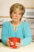 stock photo of beautiful senior woman  - Senior woman holds a coffee mug looking sad - JPG