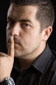 stock photo of top-secret  - Man holding a finger on his mouth - JPG