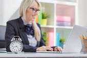 stock photo of discipline  - Hard working woman is always on time at work - JPG