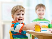 stock photo of day care center  - smiling kids painting at home or day care center - JPG