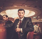 stock photo of roulette table  - Two fashionable men in suits behind table in a casino - JPG